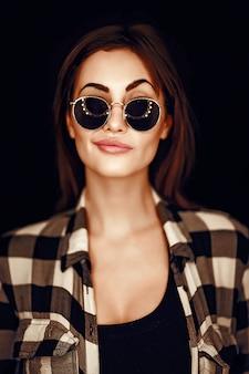 Moda bellezza donna che indossa occhiali da sole, camicia a quadri.