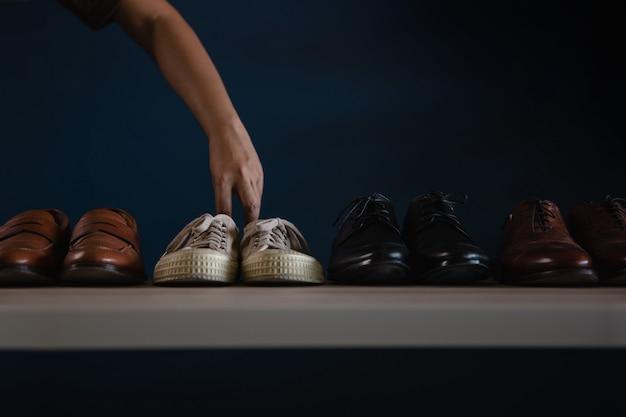 Moda calzature uomo. uomo che sceglie una scarpa da tennis da indossare. abbandona un lavoro o sii equilibrato. concetto di rilassamento
