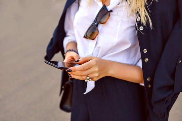 Moda da vicino i dettagli della donna che tiene il suo smartphone e tocca il massaggio, tailleur ufficiale e accessori alla moda di lusso, concentrarsi sulle mani.