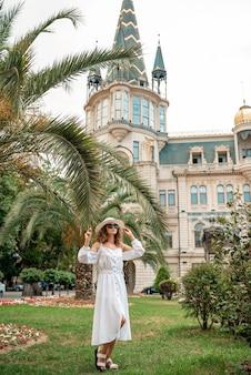 Moda di giovane ragazza bruna donna che cammina su vecchie strade. ritratto di moda di strada di giovane bella donna che cammina per la città vecchia. close up ritratto con la palma