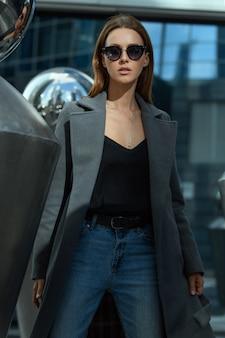 Moda donna bruna glamour in occhiali da sole e cappotto aperto grigio e camicia nera con due mani in giù sulla strada tra sculture in acciaio sotto grattacieli alti edifici della città nella riflessione di palle