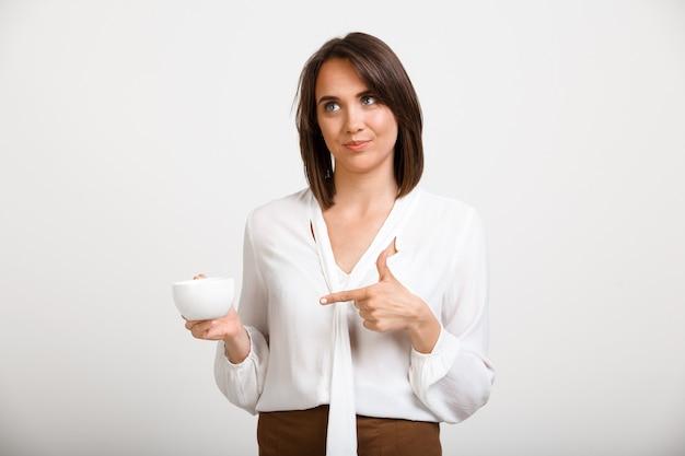 Moda donna che beve il caffè in ufficio, parlare con un collega