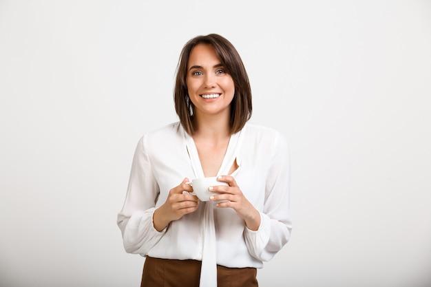 Moda donna che beve il caffè in ufficio, sorridendo felice