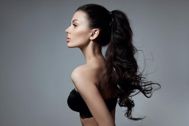 Moda donna sexy con i capelli lunghi, i capelli ricci forti di una ragazza bruna in lingerie. cosmetici naturali per la cura dei capelli, radici forti