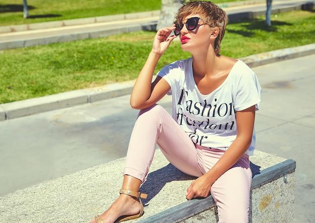 Moda elegante bella giovane donna bruna modello in abiti casual estate hipster in posa e seduto sull'asfalto