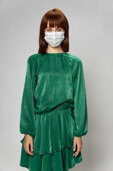 Moda femminile coronavirus, modella in posa con guanti e mascherina medica protettiva.
