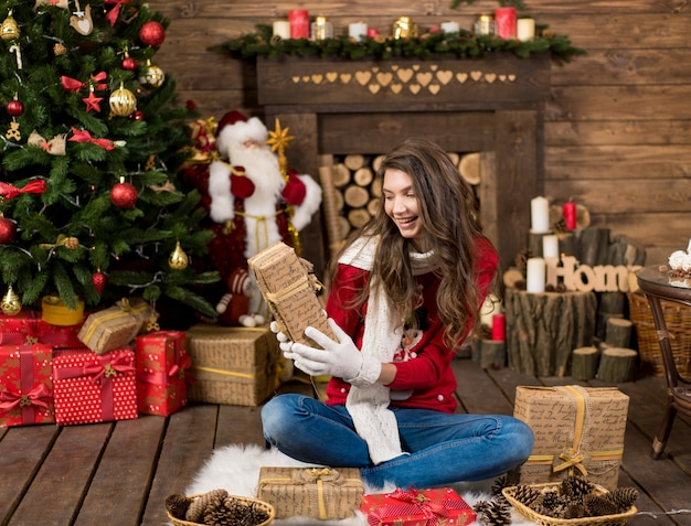 Moda giovane bellezza sposa in inverno gioiosa ragazza femminile che indossa abiti invernali, seduto vicino all'albero di natale, tenendo confezione regalo.