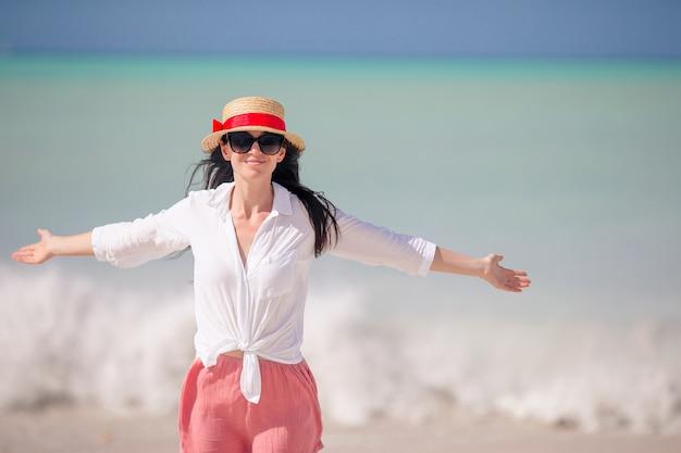 Moda giovane donna con cappello sulla spiaggia