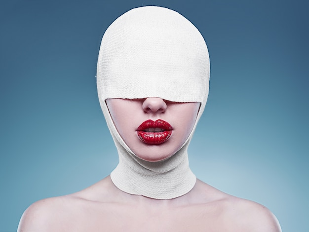 Moda giovane donna con la testa bendata e le labbra rosse