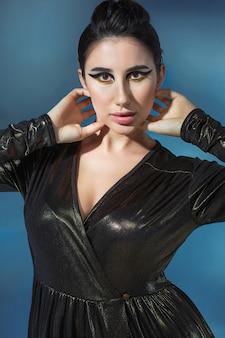 Moda giovane donna in abito elegante nero. modella glamour in posa di moda, trucco elegante