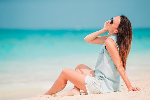 Moda giovane donna in abito verde sulla spiaggia