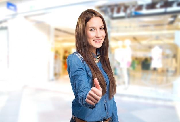 Moda giovane donna in cerca felice con il pollice in su