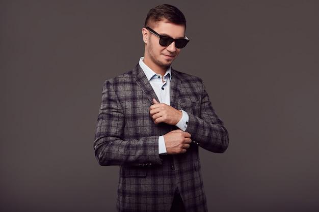 Moda giovane uomo bello con occhiali da sole alla moda