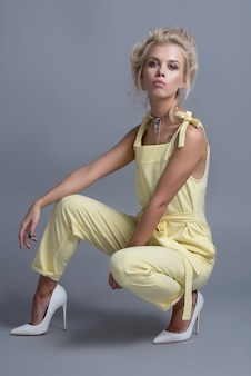 Moda giovani donne in abiti alla moda, trucco. elegante acconciatura ondulata, vestito giallo. trucco in posa vicino a una botte nera su uno sfondo grigio
