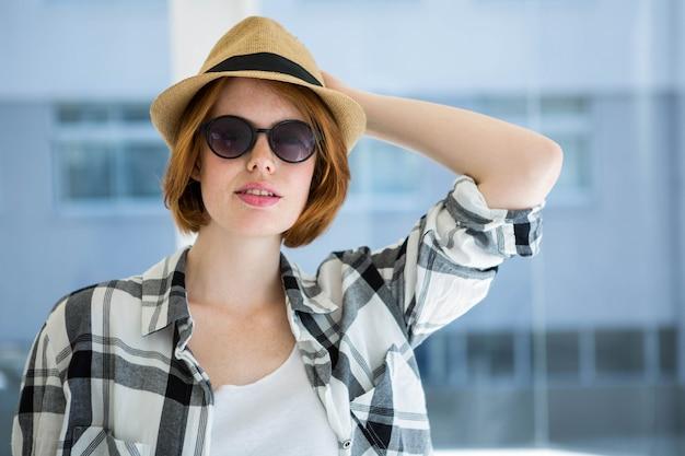 Moda hipster indossando occhiali da sole davanti a una finestra