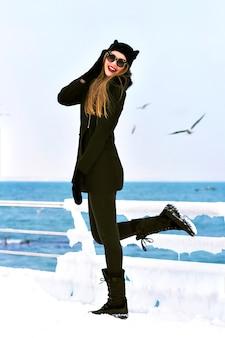 Moda inverno ritratto di elegante donna bionda signora, godersi il tempo di neve fredda al mare, ghiaccio e ventoso, cappotto nero, buffo cappello, capelli lunghi, stato d'animo sensuale, viaggiare da soli, moda invernale.
