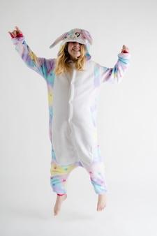 Moda moderna - bella ragazza bionda in posa su uno sfondo bianco in pigiama kigurumi, costume da coniglio