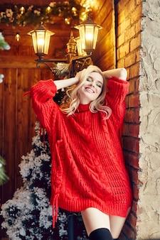 Moda natale donna bionda sexy con il maglione rosso