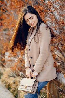 Moda ragazza che cammina in un parco di primavera