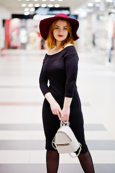 Moda ragazza dai capelli rossi usura sul vestito nero e cappello rosso con zaino da donna poste al centro commerciale commerciale.