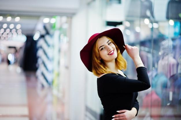 Moda ragazza dai capelli rossi usura sul vestito nero e cappello rosso poste al centro commerciale commerciale.