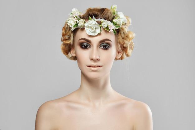 Moda ragazza modello di bellezza con fiori tra i capelli. trucco creativo perfetto e acconciatura artistica floreale.