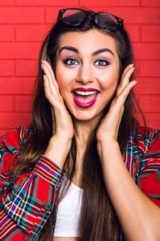 Moda ritratto al coperto di giovane donna piuttosto hipster con lunghi capelli castani e trucco luminoso, emozioni pazze sorprese, muro urbano rosso. indossa occhiali e camicia a quadri.