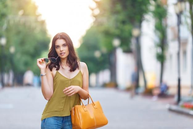 Moda ritratto di città di donna elegante hipster con borsa, abito naturale, trucco, capelli lunghi bruna, camminando da sola nel fine settimana, goditi le vacanze in europa