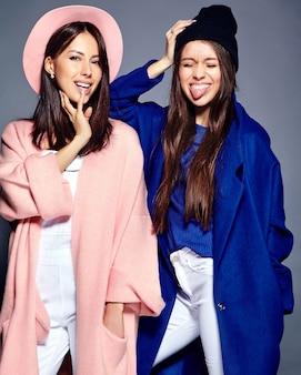 Moda ritratto di due modelli sorridenti delle donne del brunette nella posa casuale del cappotto dei pantaloni a vita bassa di estate