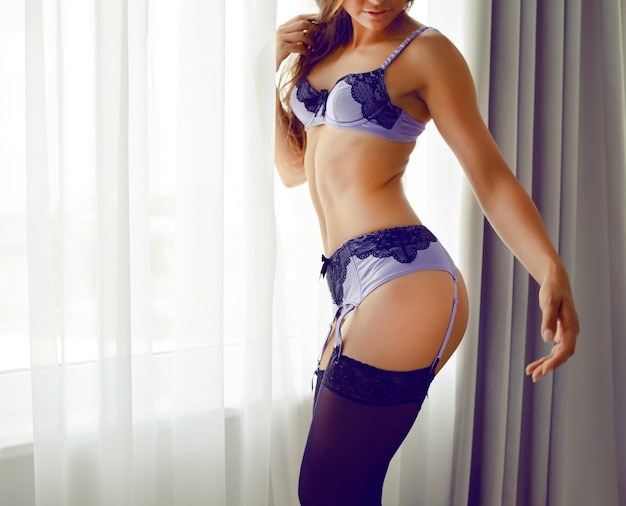 Moda ritratto os giovane donna sexy con perfetta figura sportiva snella, indossando lingerie bella ed elegante, in posa da solo vicino alla finestra. stile boudoir, atmosfera romantica.
