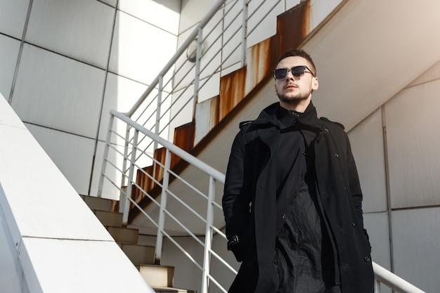 Moda uomo in total black, in piedi sulle scale, guardando lontano.