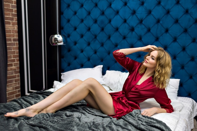 Modella bionda abbastanza sensuale sdraiata sul letto, godersi la mattinata in un hotel di lusso, indossando camicia da notte e vestaglia di seta bordeaux, capelli ciechi e viso di bellezza, stile boudoir.