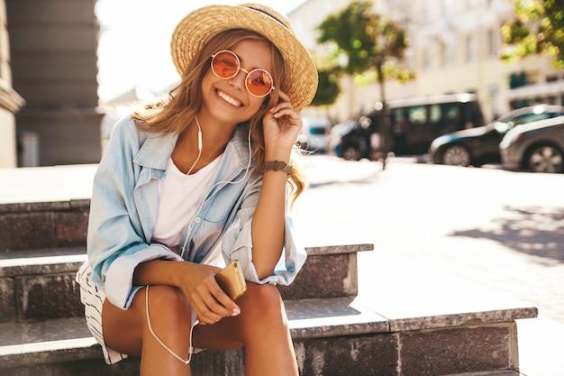 Modella bionda in abiti estivi in posa sulla strada ascoltando musica