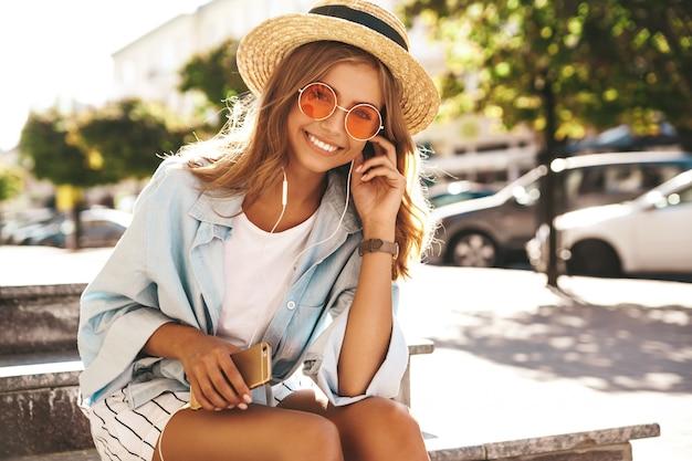 Modella bionda in abiti estivi in posa sulla strada
