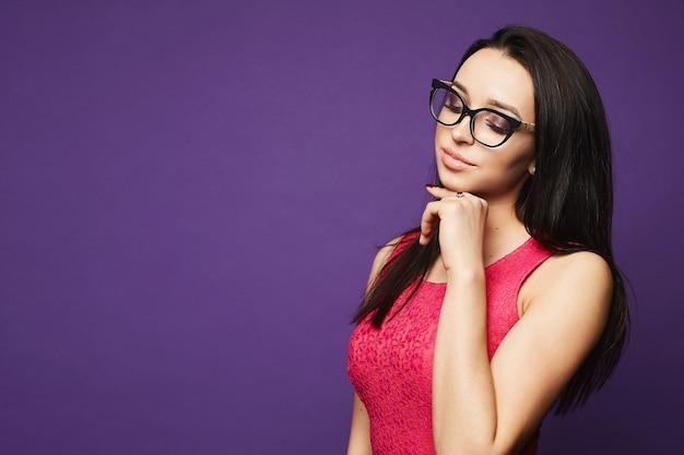 Modella bruna con il trucco con gli occhiali neri e abito rosa a parete viola