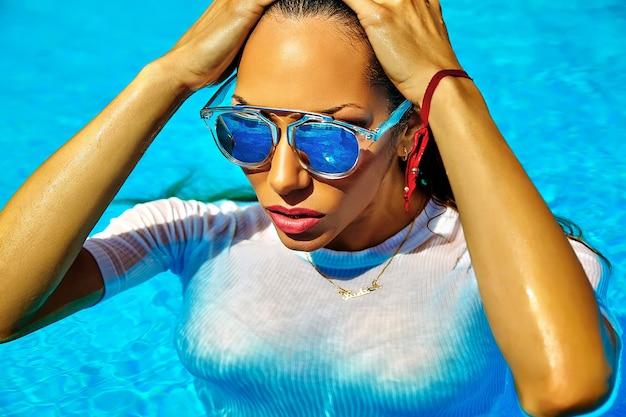 Modella con i capelli scuri in costume da bagno bianco che esce dalla piscina