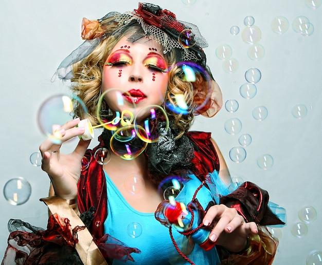 Modella con trucco creativo che soffia bolle di sapone.