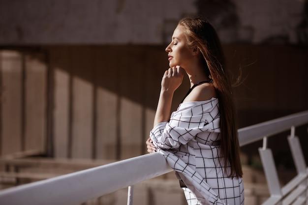 Modella con una bella figura in abito bianco in città in estate. il sole splende. moda in città. spazio marrone, concetto