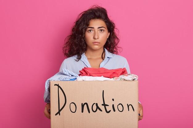 Modella delusa dai capelli ricci che indossa camicia blu, con espressione facciale sgradevole, con scatola con iscrizione donazione, arrabbiata. concetto di persone e gentilezza.