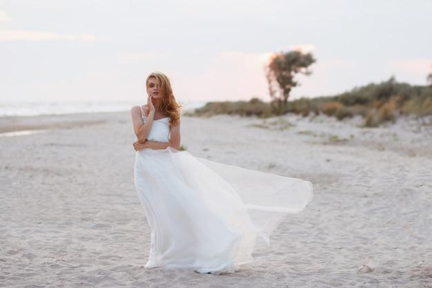 Modella in abito bianco la sera sull'oceano. il vento sviluppa i capelli e il vestito. tenera foto estiva. sfondo sfocato. sola ragazza romantica