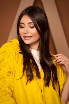 Modella in felpa con cappuccio in cotone giallo, capelli aperti