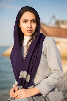 Modella in riva al mare che copre la testa con uno scialle nero e seduto sulle pietre