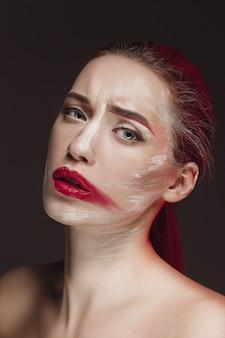 Modella ragazza con la faccia colorata dipinta. ritratto di arte moda bellezza di bella donna con il trucco astratto colorato.