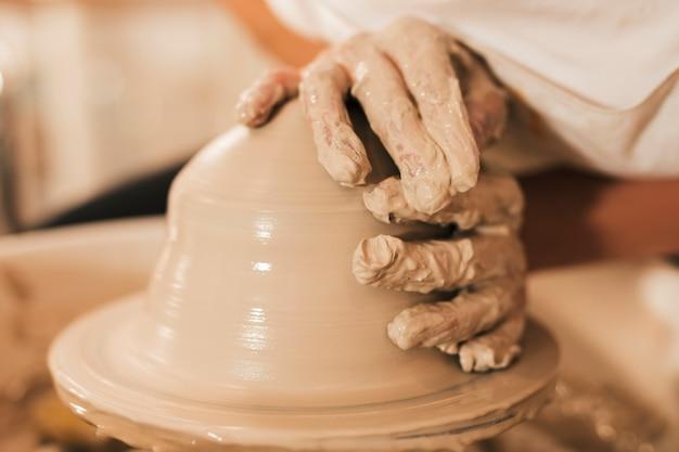 Modellazione di argilla su un tornio nell'officina di ceramiche
