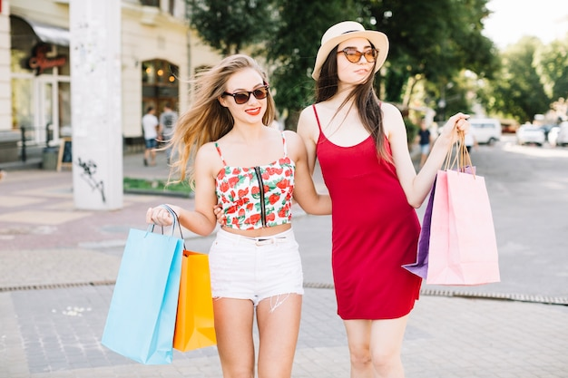 Modelli alla moda sicuri che camminano con i sacchetti