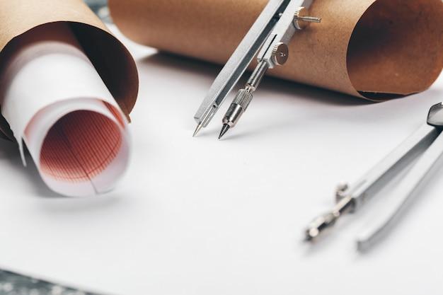 Modelli architettonici e rotoli del modello e strumenti di disegno sul piano di lavoro.