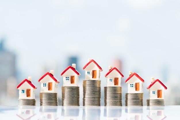 Modelli di casa in cima alla pila di monete con sfondi di città.
