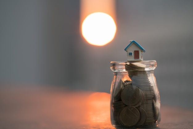 Modelli di casa sulla cima di barattolo di monete con sfondi tramonto.