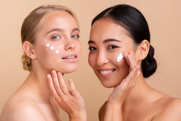 Modelli di close-up con crema per il viso in posa insieme