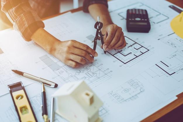 Modelli femminili del disegno dell'architetto nel posto di lavoro dell'ufficio.